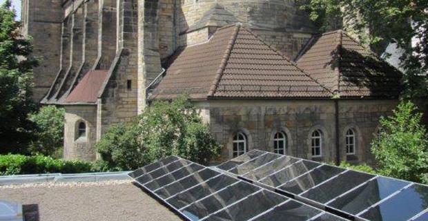 Solarzellen auf einem Dach, im Hintergrund eine Kirche