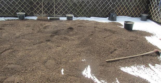 Schotter und Erde werden auf der Terrasse verteilt