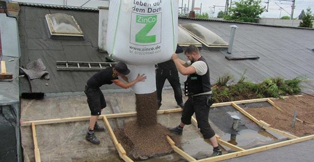 Erde wird mit einem Kran auf ein Dach geschüttet